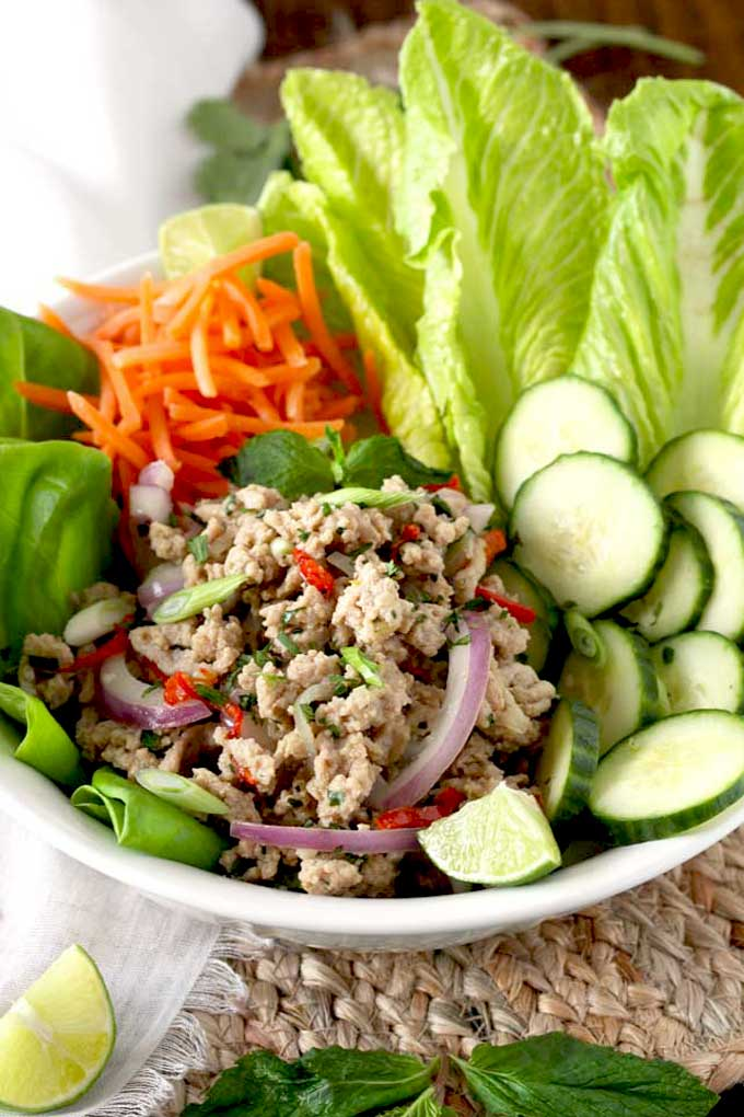 Thai Larb salad served with vegetables in a white bowl.