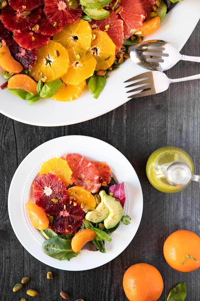 Citrus Fruit Salad with the best basil dressing on a white plate.