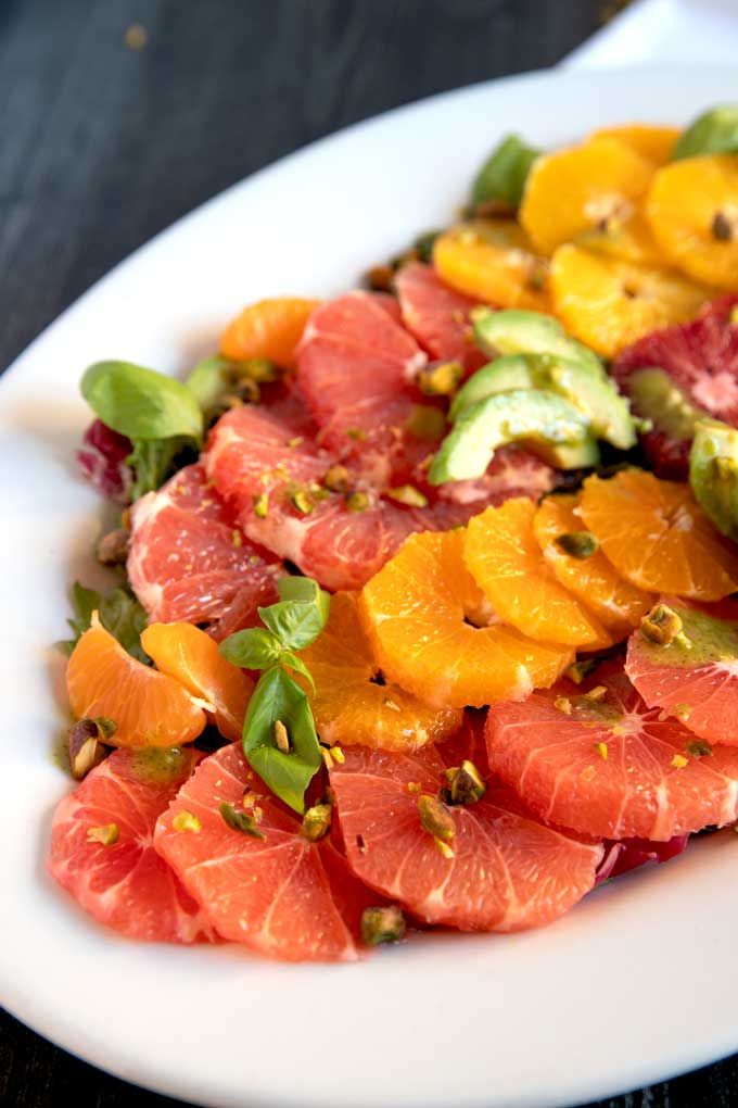 Peeled and sliced citrus fruit, oranges, grapefruit, pomelos with avocado slices and basil leaves on a white plate.