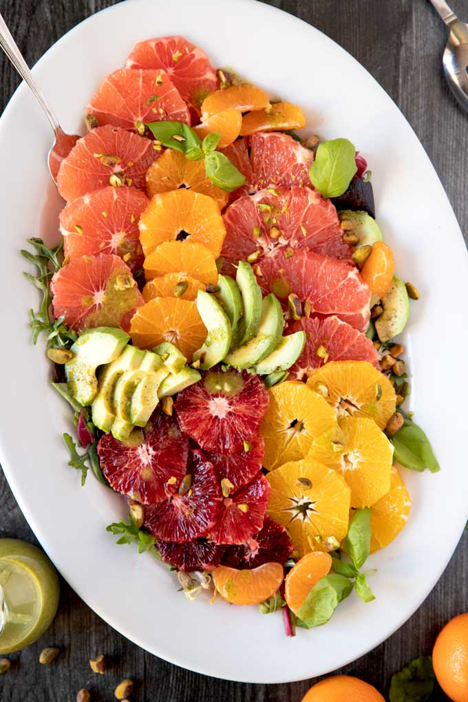 A platter filled with citrus fruits on a bed of salad greens.