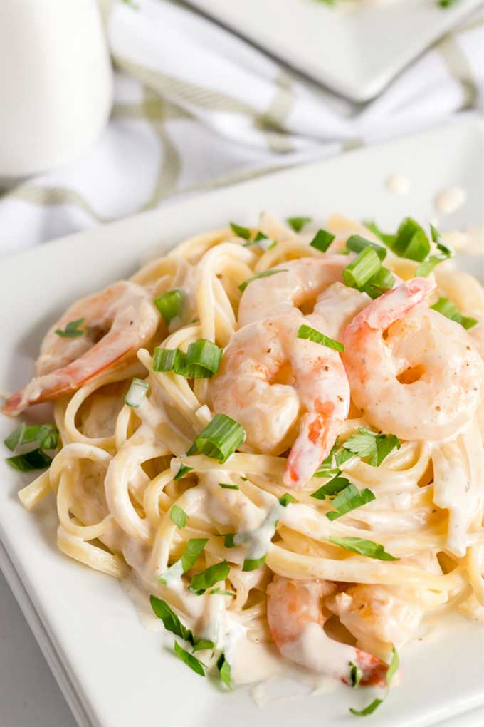 SHRIM AND HOME MADE PASTA TOSEED IN  CAJUN ALFREDO SAUCE ON A WHITE PLATE