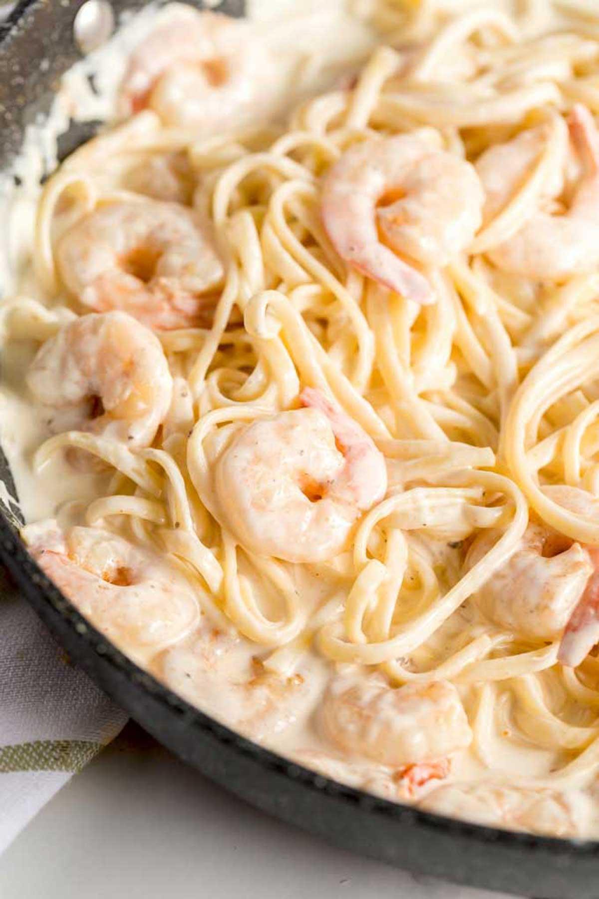 Creamy Cajun Alfredo Shrimp Pasta in a skillet.