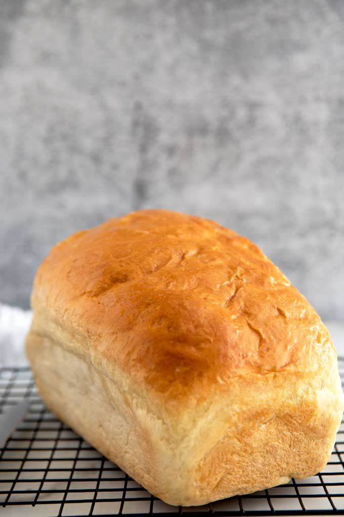 A loaf of homemade white bread on a cooling rack,