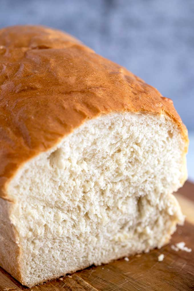 Soft and fluffy white bread with the most tender crumb on a cutting board.