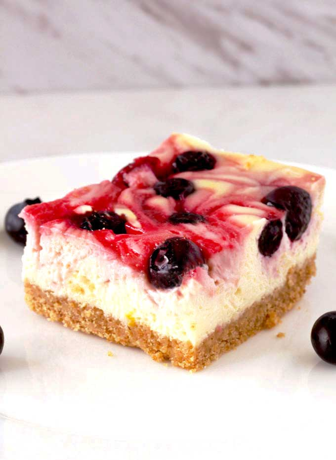 A berry swirl cheese cake bar on a white surface