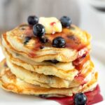 Fluffy Blueberry Pancakes Stacked up and drizzled with blueberry syrup.