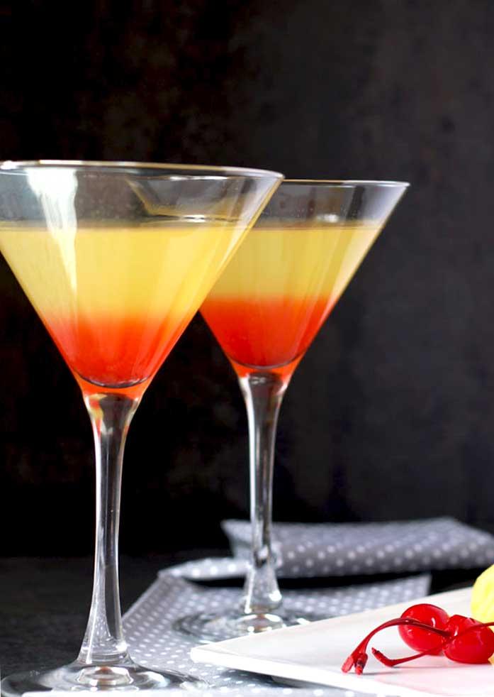 Two martini glasses filled with colorful Bikini vodka martini