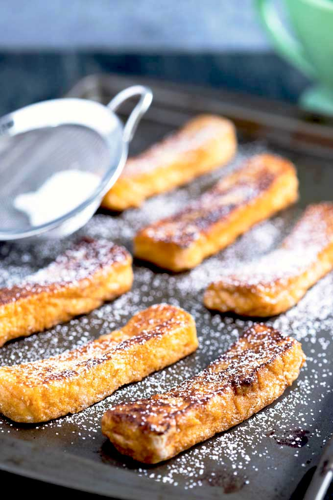 Homemade Cinnamon sticks on a sheet pan getting dusted with powdered sugar