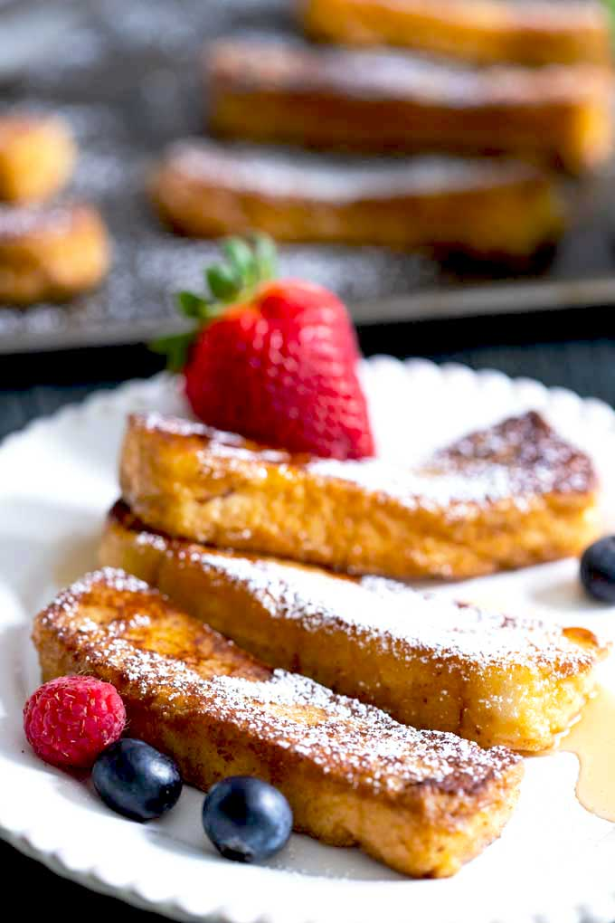 Cinnamon French Toast Sticks served on a white plate with berries and maple syrup.