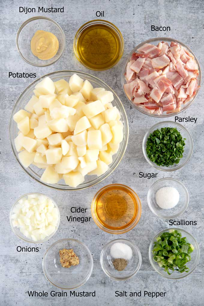 Ingredients to make German Potato Salad on a gray surface.