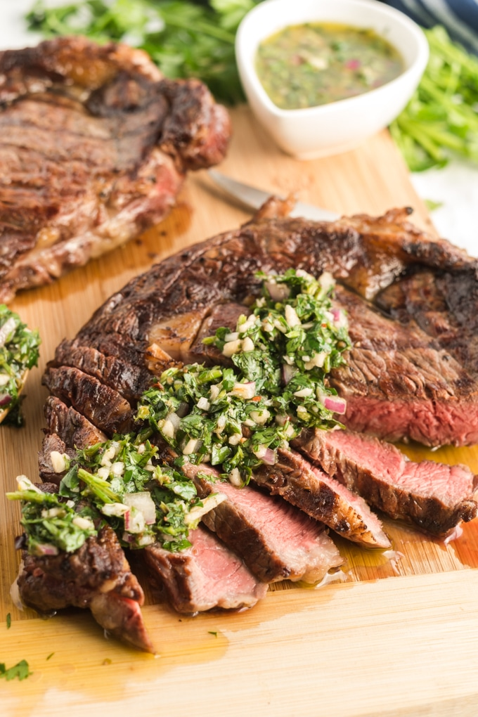Grilled Steak sliced and topped with chimmichurri sauce on a cutting board.