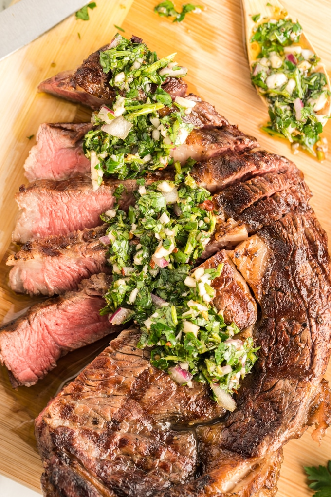 Sliced ribeye steak topped with Chimichurri on a cutting board.