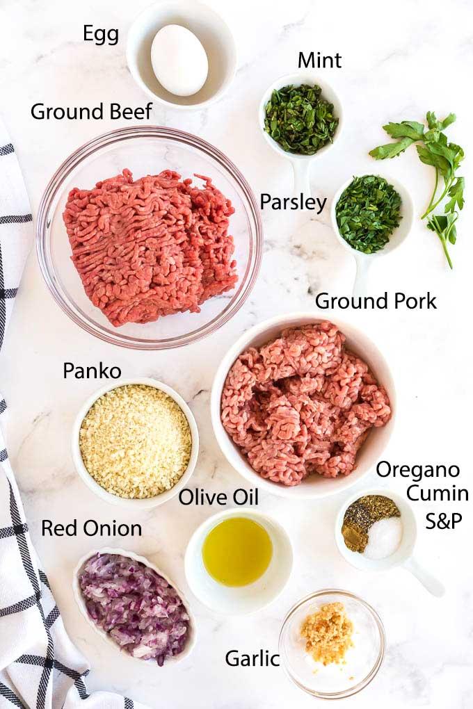 Ingredients to make Greek Mediterranean Meatballs on a white sourface.