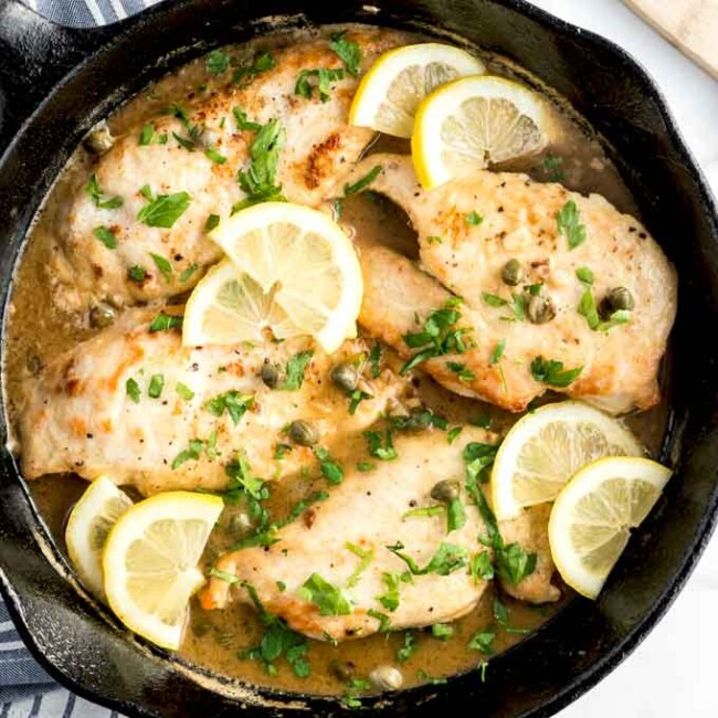 Delicious Italian Chicken Piccata with lemon slices and capers in a skillet.