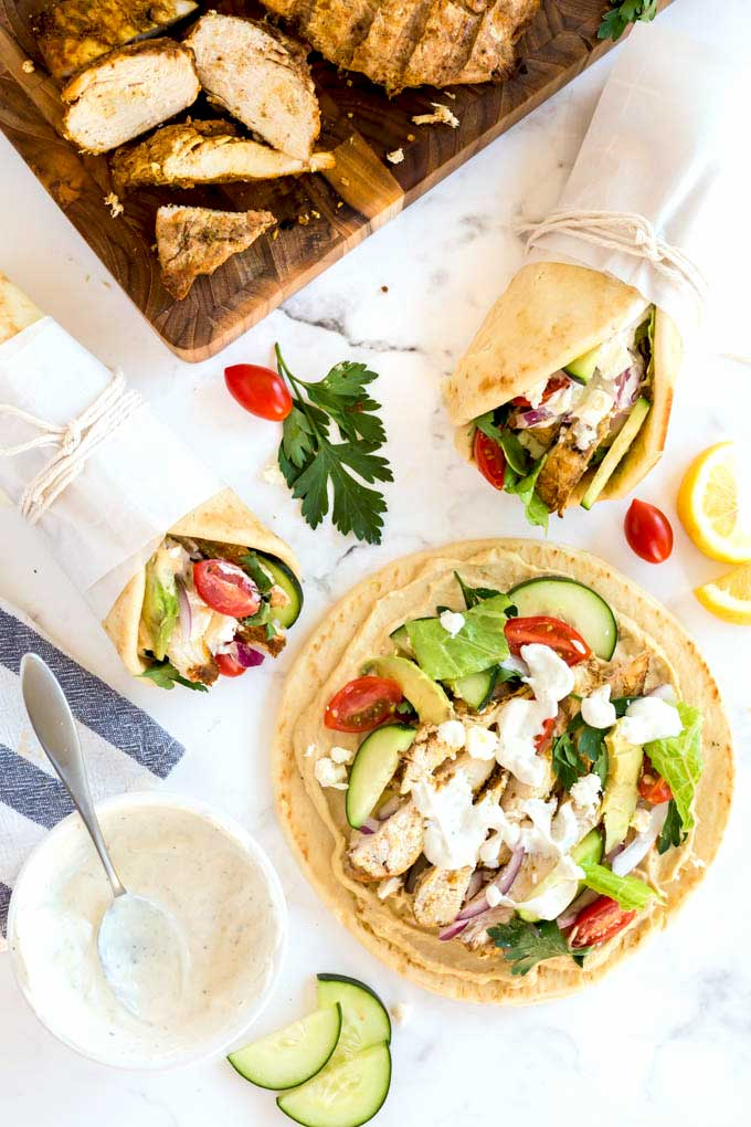 Chicken wraps and flatbread topped with hummus, chicken, yogurt sauce and veggies.