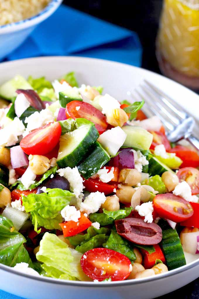 Crisp Chopped Greek Salad with Kalamata olives and Feta cheese on a white bowl.
