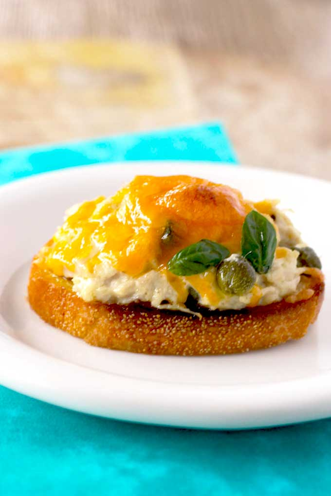 Crostini topped with tuna salad and melted cheese resembling a tuna melt.