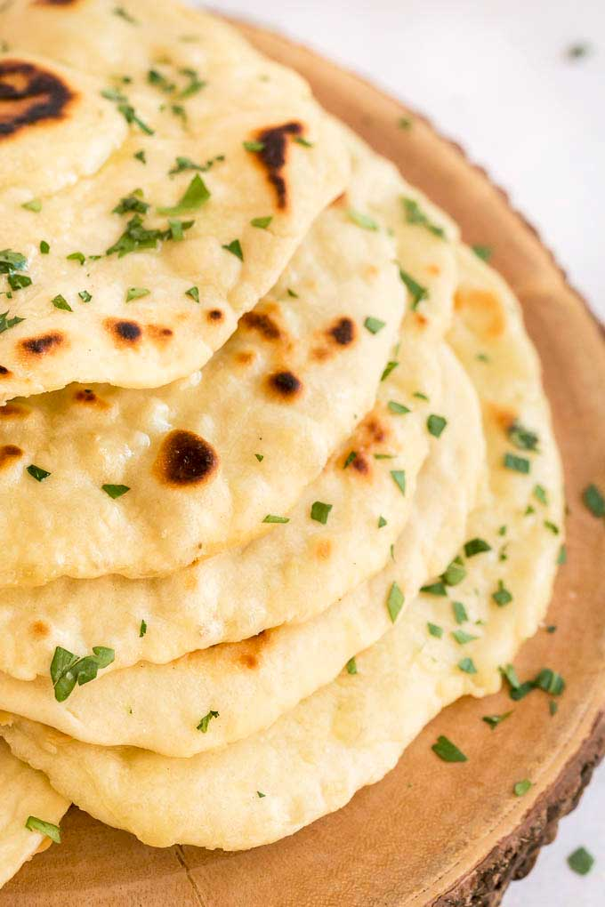 A stack of flatbread on a wooden surface.