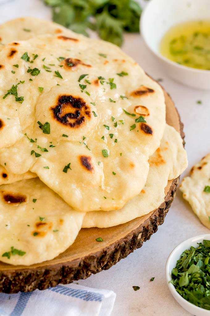 Flatbreads brushed with butter on a wooden block
