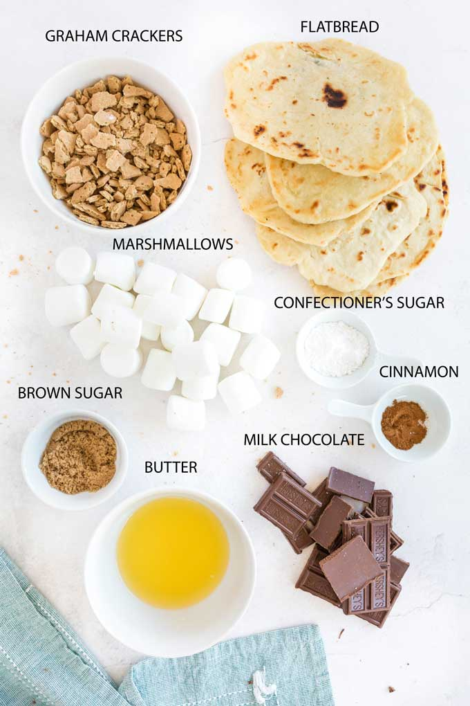 Ingredients to make s'mores flatbread on a white surface.