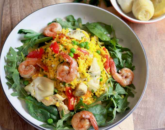 Top view of a bowl filled with shrimp and chicken paella salad.