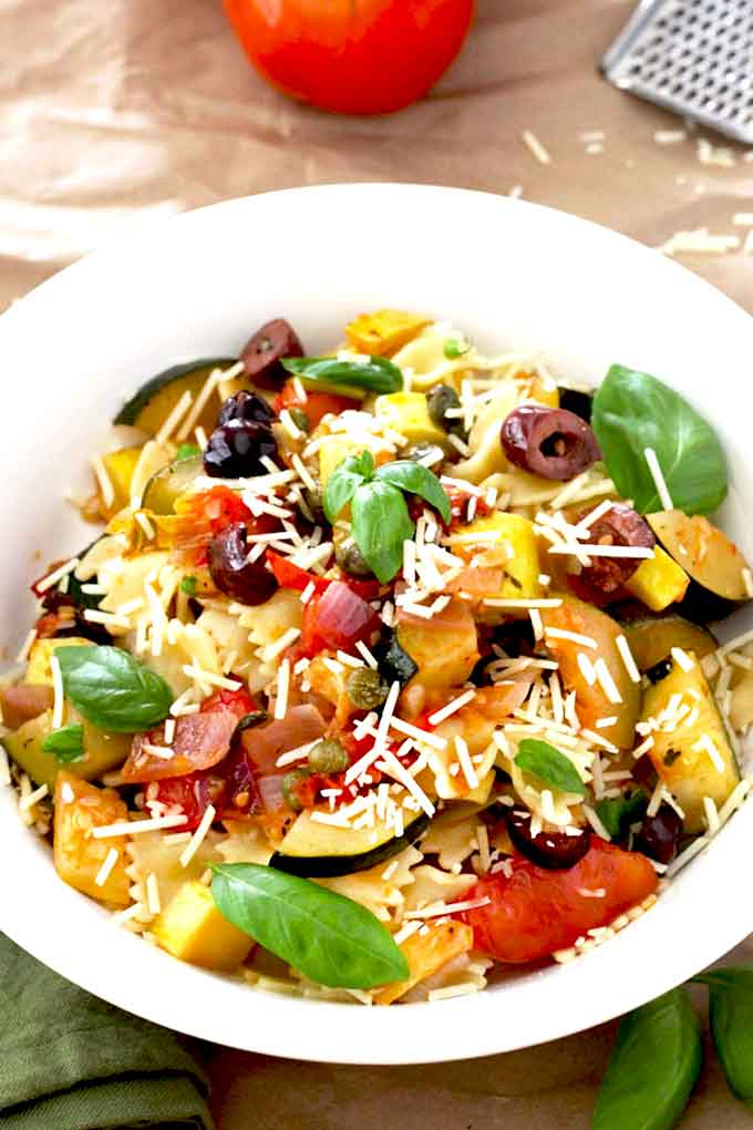 A white bowl filled with veggie pasta and top with Parmesan cheese.