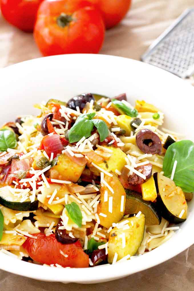 Saute vegetable pasta with basil and Parmesan cheese in a white bowl.