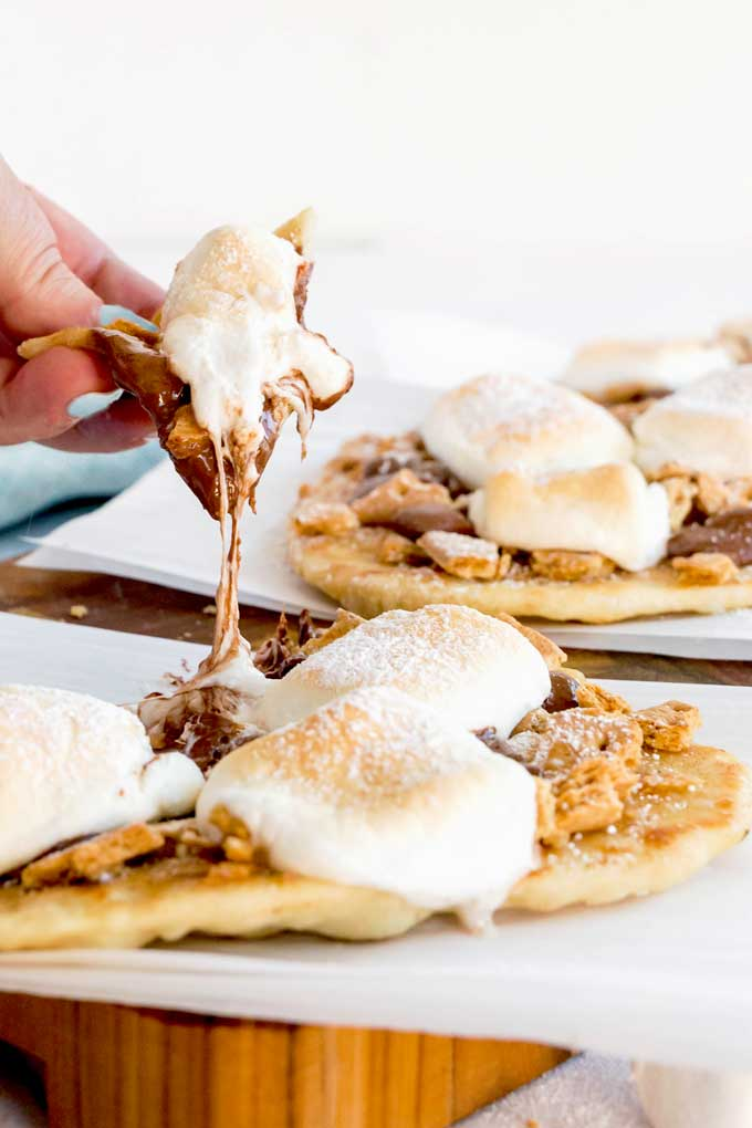 This photo shows someone pulling a piece of ooey gooey melted chocolate and marshmallow s'mores flatbread