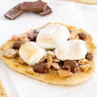 Hot off the oven s'more flatbread dessert pizza on a white surface