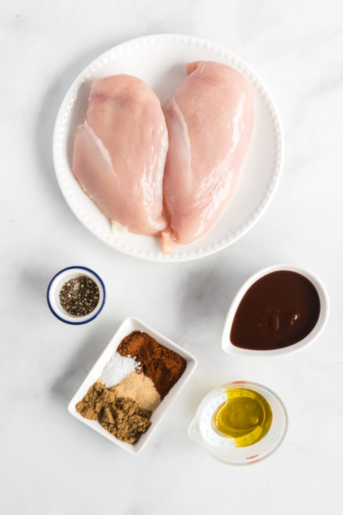 Ingredients to make BBQ Chicken on a light surface.