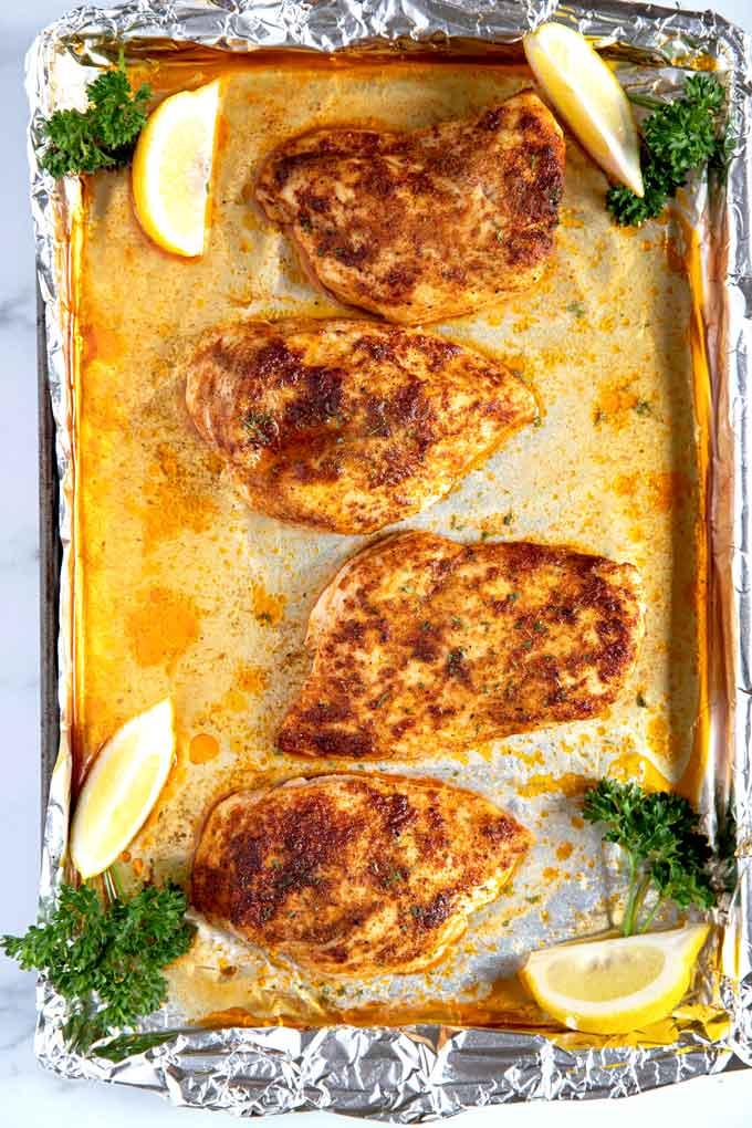 Boneless skinless chicken breasts seasoned on a baking sheet pan.