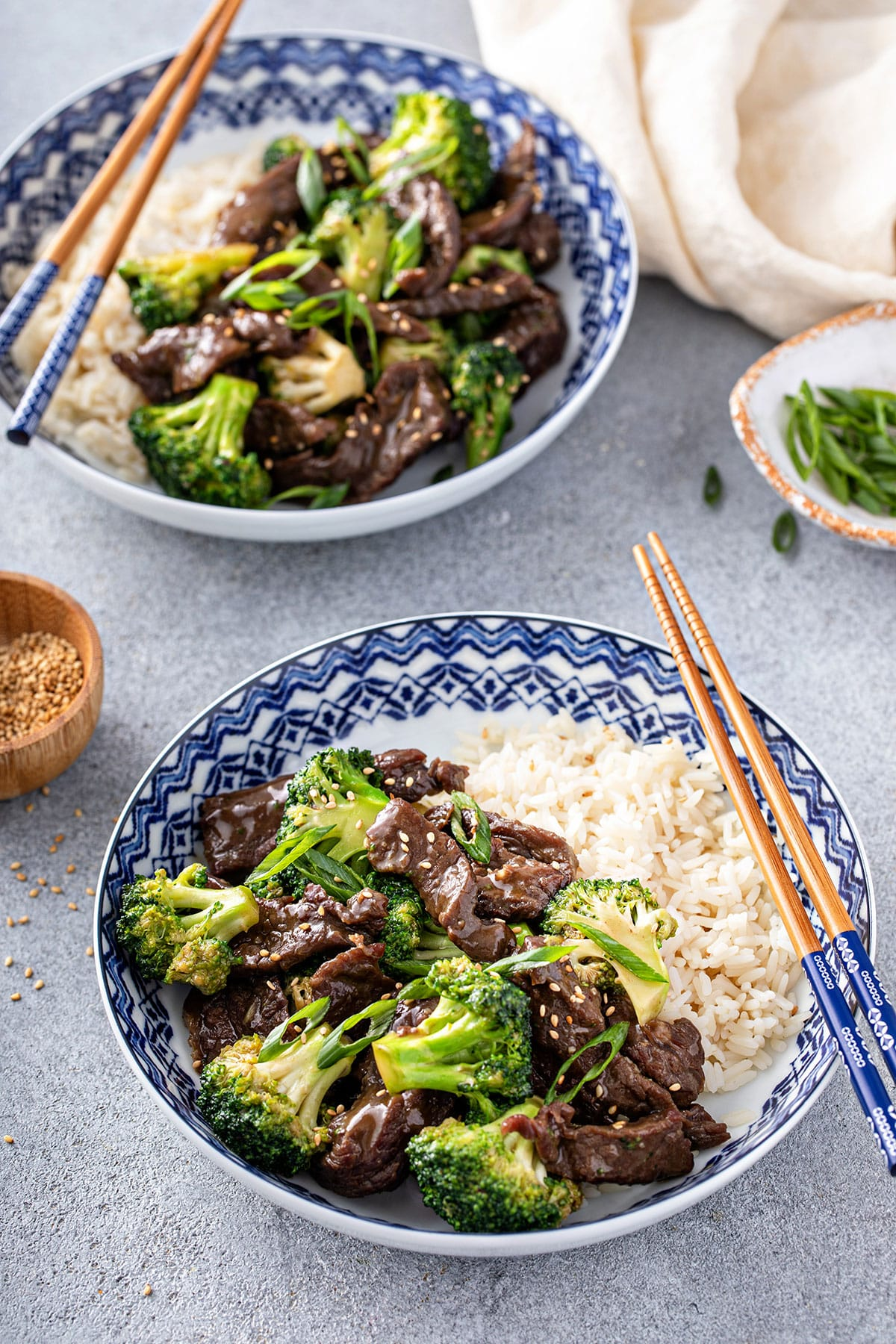 Chopsticks starting to lift broccoli beef from a white bowl.