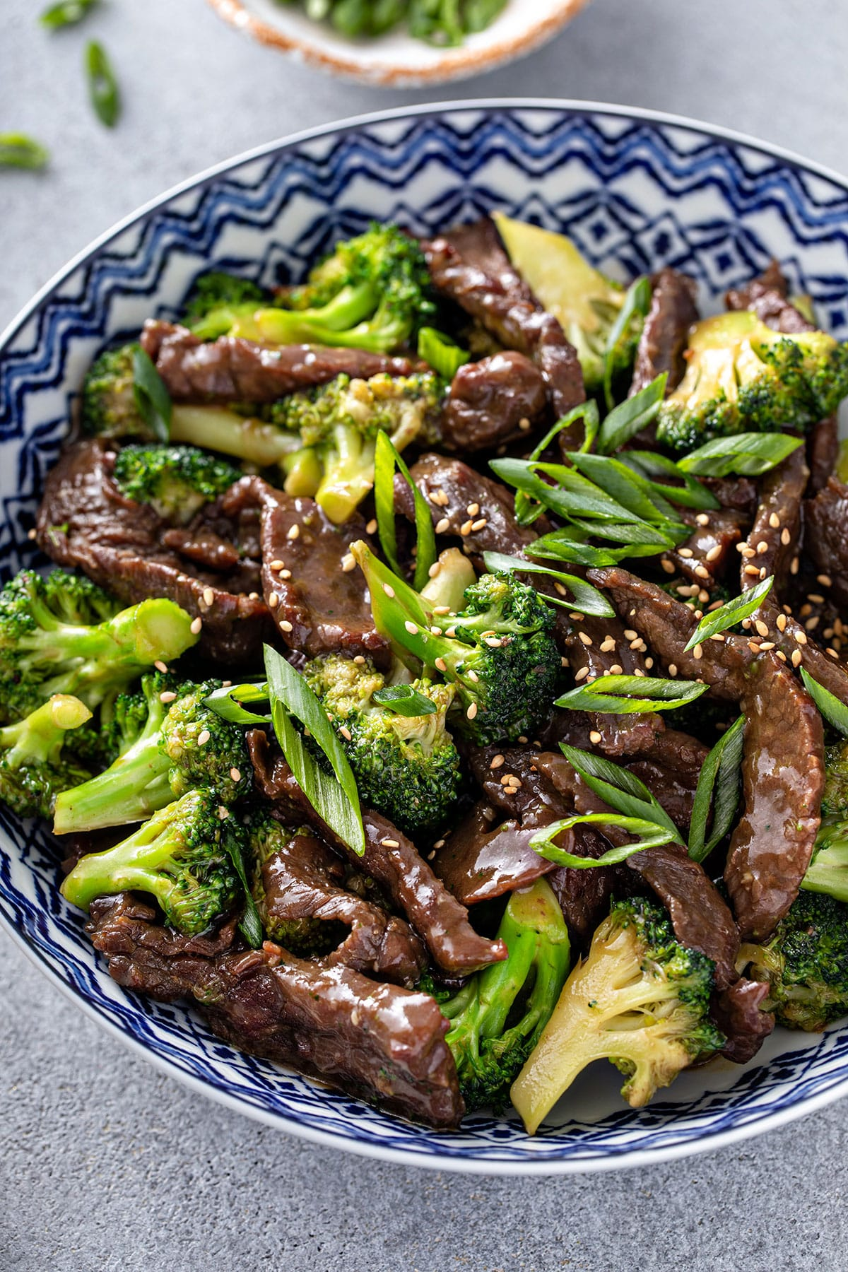 A tender thin sliced beef piece lift by a chopstick from a white bowl filled with Broccoli Beef