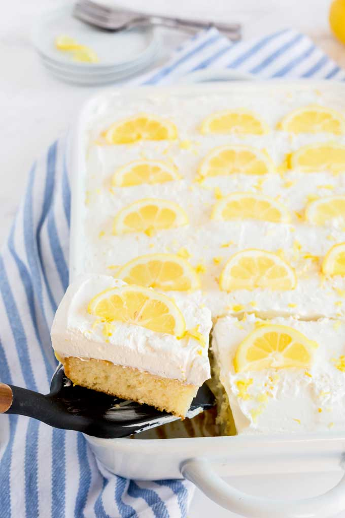 Lifting a piece of lemon cake with a spatula from a baking dish