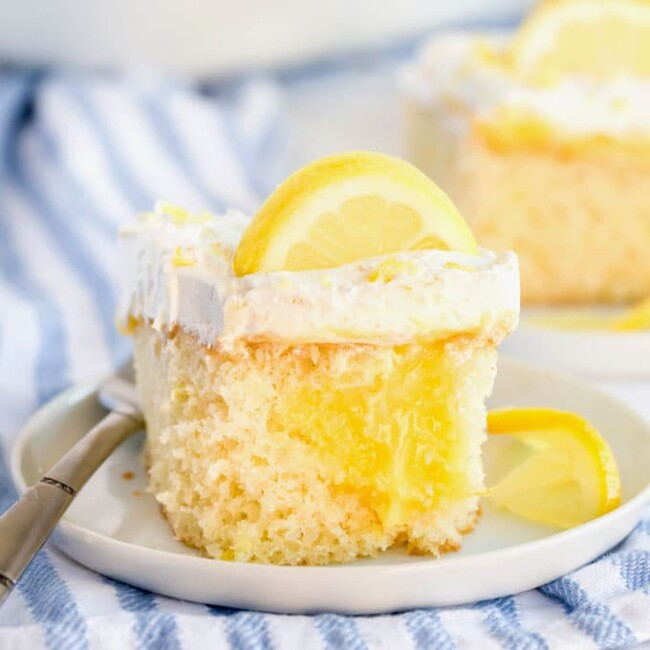 A piece of lemon poke cake garnished with lemon slices on a white plate