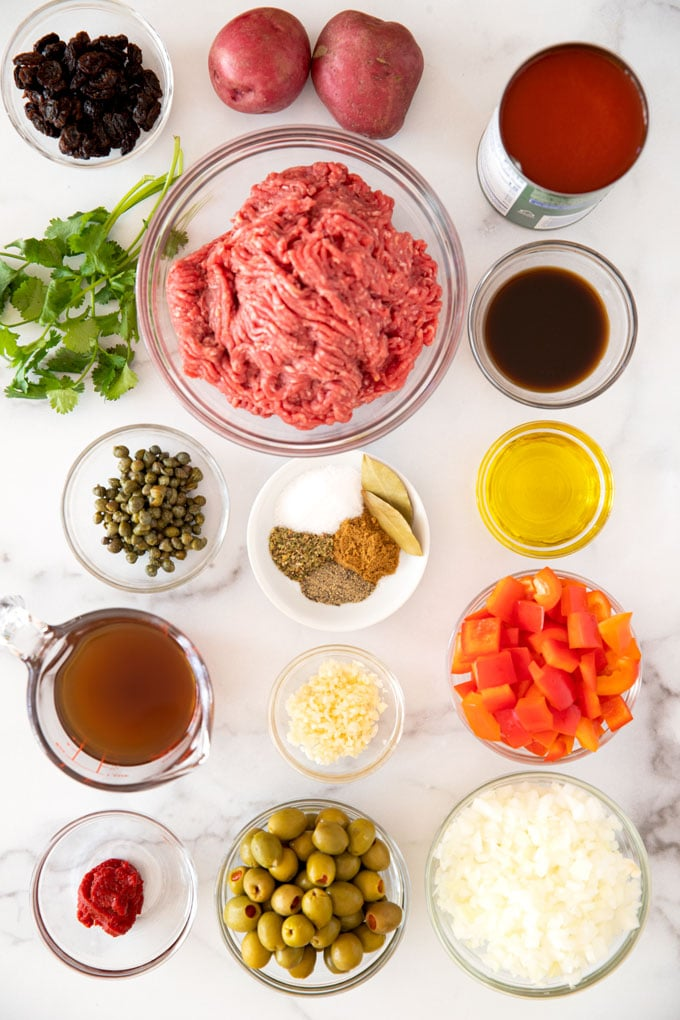 Picadillo ingredients set in bowls on a marble counter.