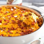 Cheesy pasta bake scooped from a white skillet.