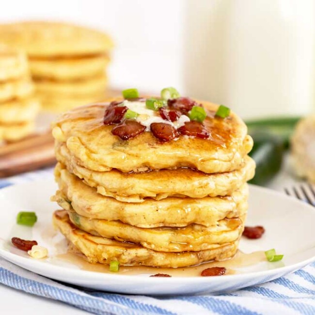 A stack of pancakes topped with bacon and maple syrup.