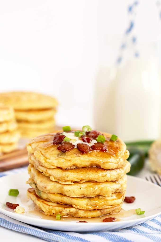 A stack of sweet pancakes topped with crispy bacon and butter on a white plate.