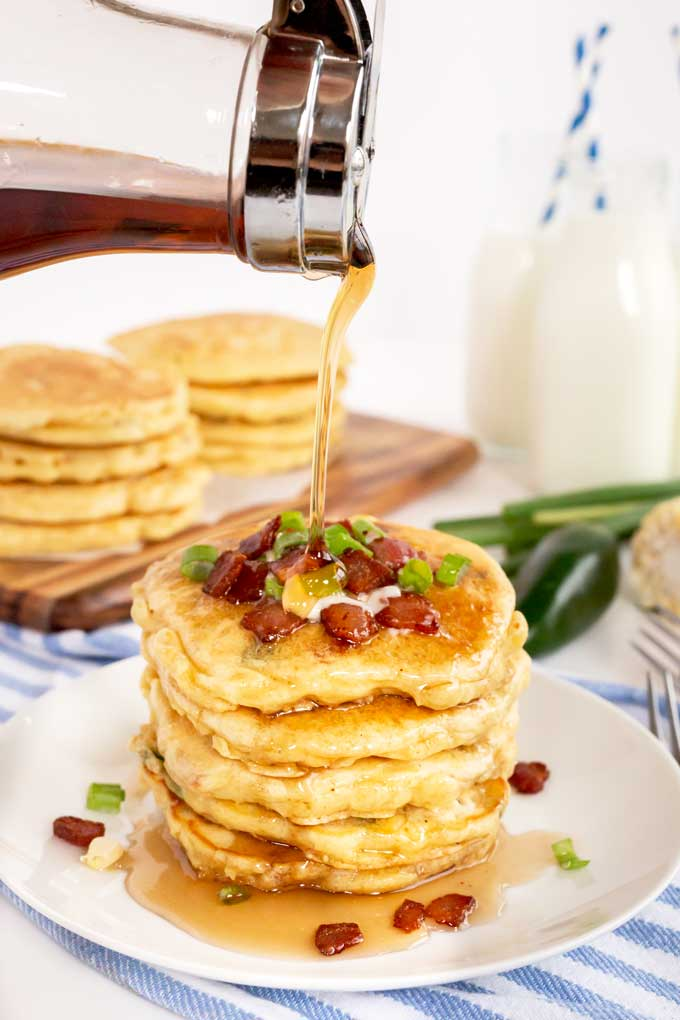 Warm maple syrup pouring on a stack of pancakes topped with bacon.