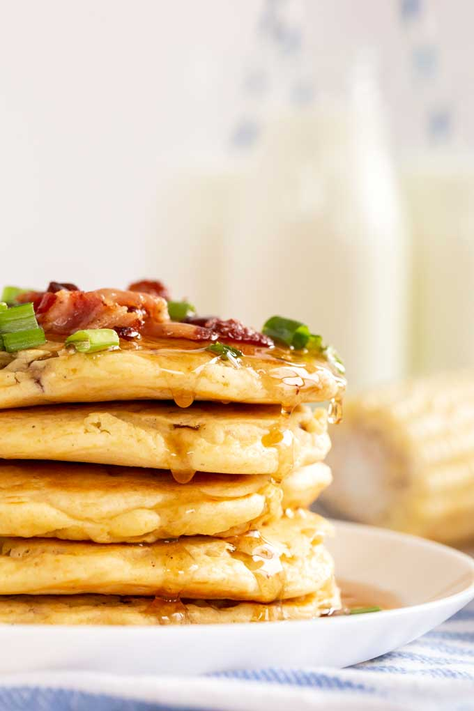 Closeup of the side of a stack of corn hotcakes on a white plate
