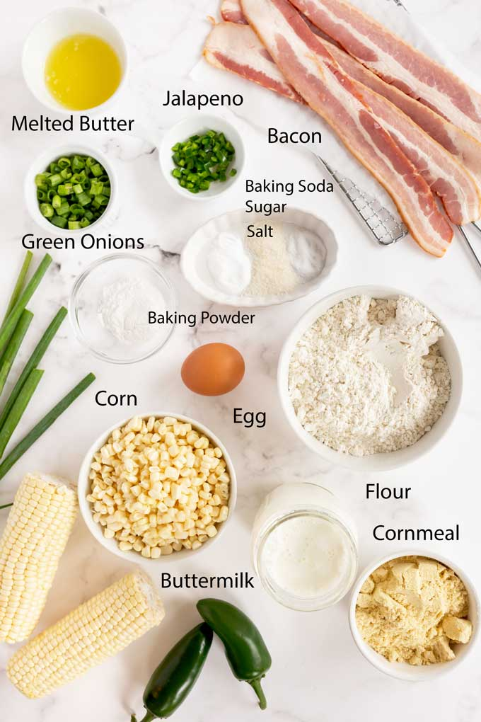 Ingredients to make corn pancakes with bacon on a white marble surface.