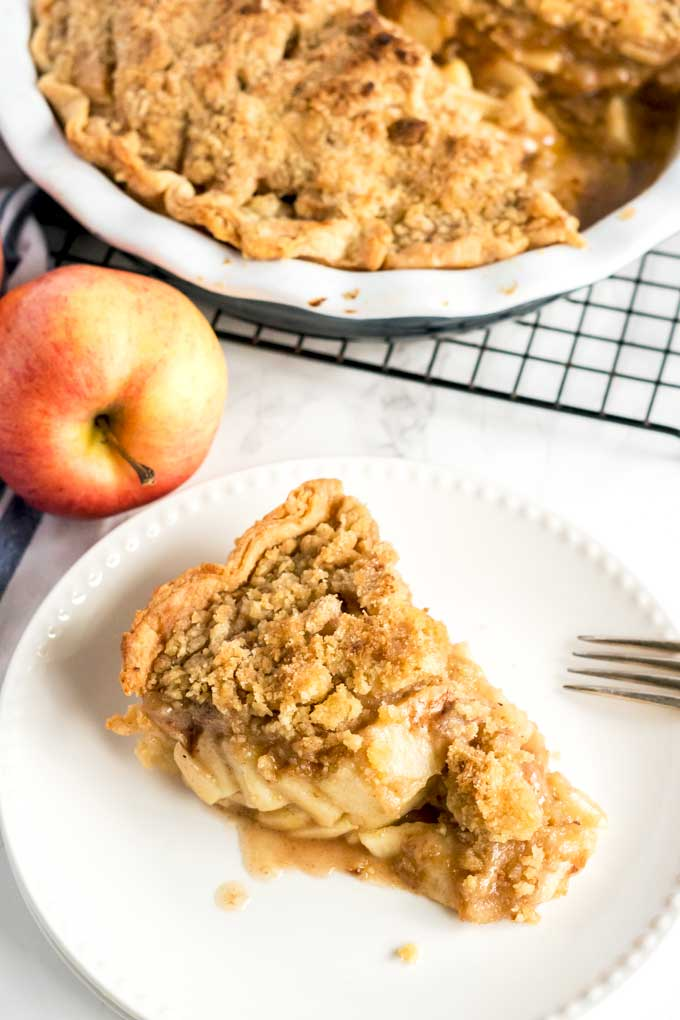 Apple pie slice with streusel crumble topping on a white plate.