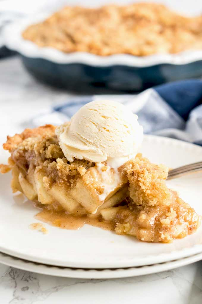 Apple Pie with streusel topping on a white plate.