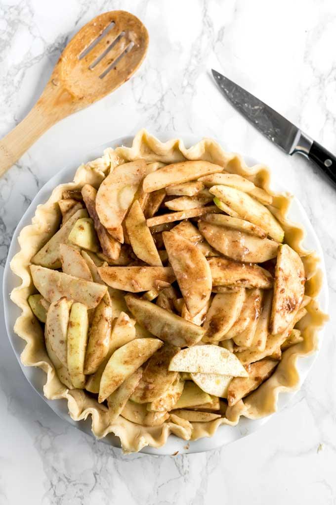 Apple pie filling in an unbaked pie shell.