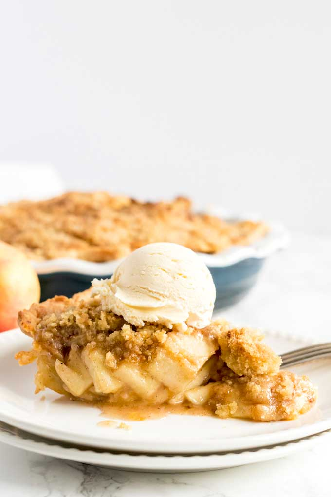A slice of Dutch apple pie topped with vanilla ice cream