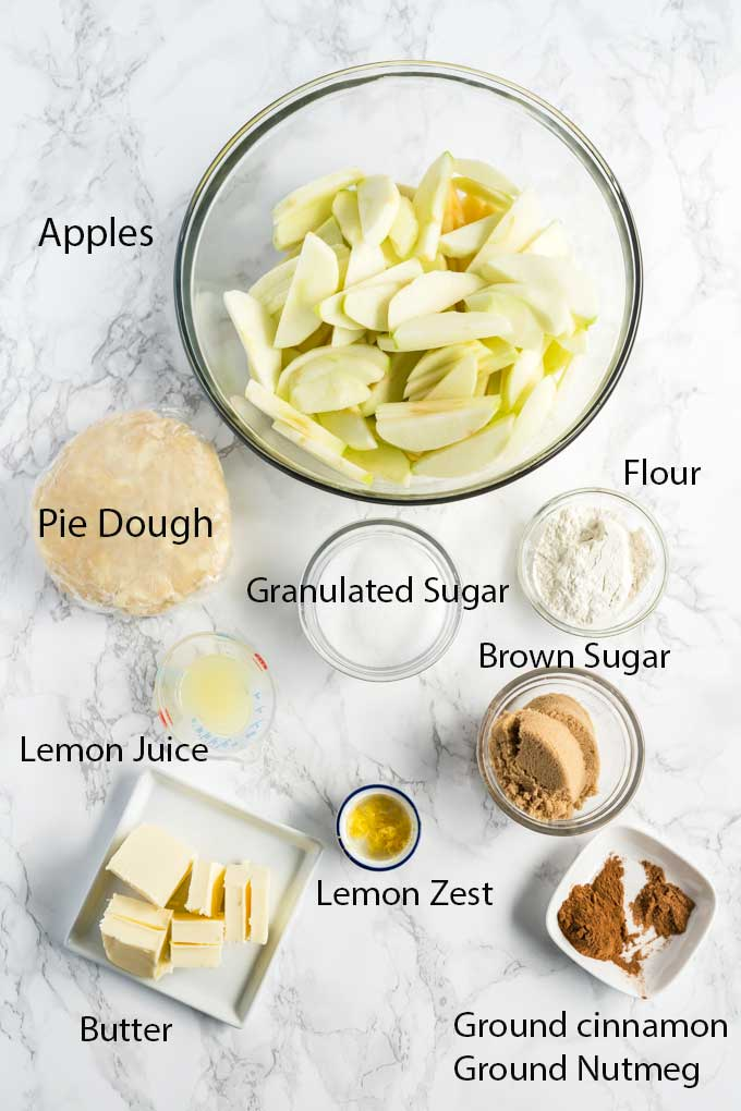 Ingredients for making apple crumble pie on a white surface.