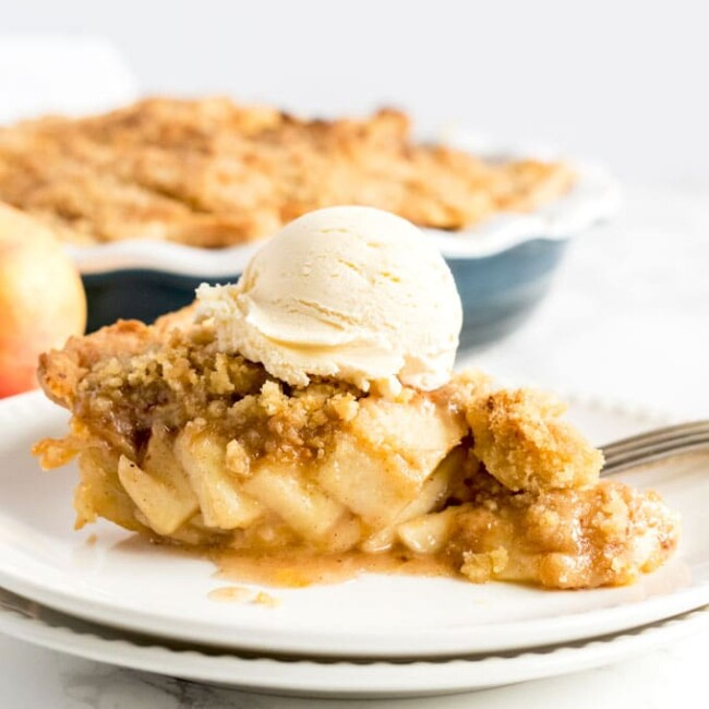 A slice of Crumble Apple Pie topped with vanilla ice cream on a white plate