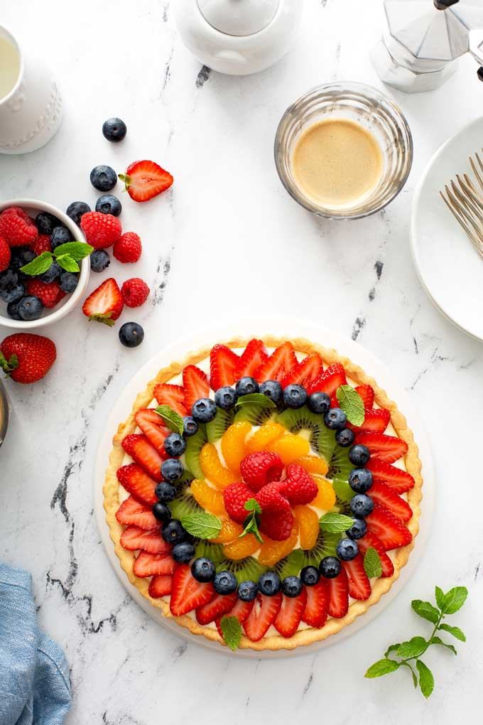 Top view of fresh fruit tart on a white platter.