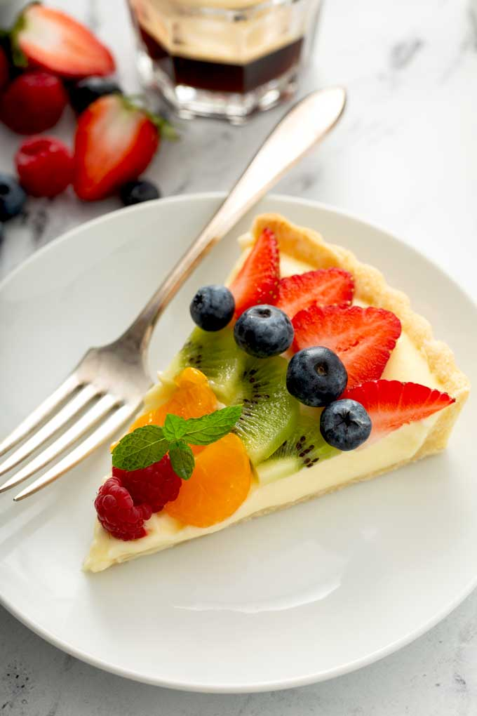 A slice of the best fruit tart on a white plate.